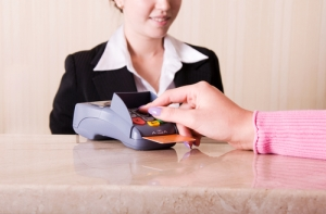 person using chip card reader with business woman in background